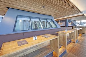 Als Parallelogramme gefertigte Verglasungen erlauben aus dem Restaurant einen Blick auf die Seilbahntechnik