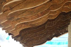 Die hölzernen, sich verjüngenden Verzierungen bleiben unter den Dachüberständen erhalten