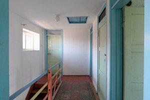 Historisch sparsam erbaut: Die Holztreppe mit einem Seil als Handlauf, der Fußbodenbelag im Obergeschoss aus Stragula, einer preiswerten Linoleum-Imitation aus mit Teer imprägnierter Wollfilzpappe, mit Ölfarbe aufgedrucktem Teppichmuster