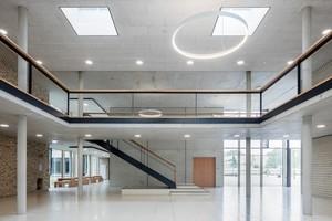 Lichtdurchflutetes, großzügiges Foyer mit Treppe und Blick auf den Gebäudeteil, der die Fachräume der Gesamtschule Lippstadt bündelt