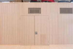 Die zweiflügelige Schörghuber Tür ist wie die umliegenden Wände mit Buchenfurnier beplankt und integriert sich flächenbündig und somit nahezu unsichtbar in den Raum