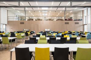 """Blick von der Mensa hoch zur verglasten Front der Mediathek, im Hintergrund die nahezu unsichtbar in die Wand integrierten Türen von Schörghuber, die zur Essenausgabe führen<span class=""""bildnachweis"""">Fotos: Hörmann / Schörghuber</span>"""