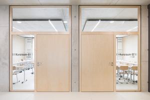"""Rechts: Schörghuber Türen mit vollflächig verglasten Seitenteilen und Oberlichtern führen in die Klassenräume<span class=""""bildnachweis"""">Fotos: Hörmann / Schörghuber</span>"""