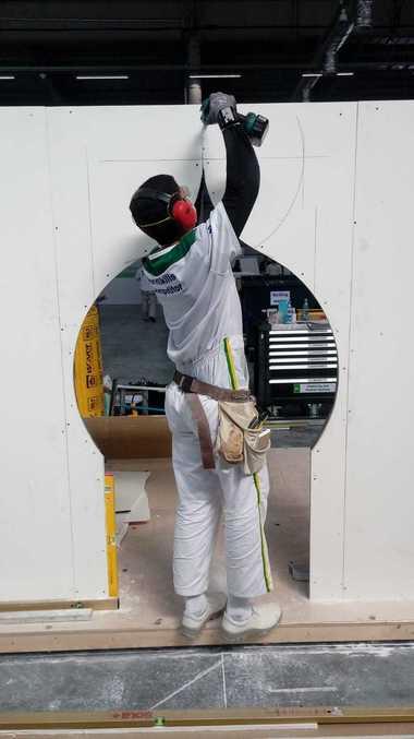 Der brasilianische Teilnehmer verschraubt eine Platte auf der Metall-Unterkonstruktion. Als Ausschnitt hat die Jury einen Zwiebelturm vorgegeben, eine Form, die man in Kazan häufig findet.<br />