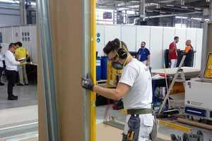 Auf einer 3x3 m großen Bodenplatte bauen die Stuckateure eine 2,1x2,1x2,1 m große Unterkonstruktion aus Metallschienen und Gipsplatten. Ein kleiner Raum entsteht - mit Ausschnitten für Türen, Fenster und Technik.