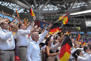 Die deutschen Fans auf der Tribüne - darunter Freunde, Trainer, Familien, Teammitglieder - feiern den Einmarsch ihrer Schützlinge auf der Tribüne