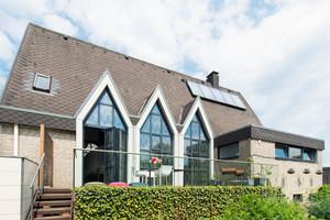"""Aus einer 1980 in Hasbergen bei Osnabrück erbauten Kirche wurde ein Wohnhaus. Charakteristisch für das Gebäude sind die spitzen Kirchenfenster. Auf den ersten Blick vermutet man nicht, dass es sich dabei um eine Glas-Faltwand handelt<span class=""""bildnachweis"""">Fotos: Solarlux / Bettina Meckel</span>"""