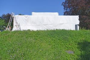 Um eine zu schnelle Durchtrocknung durch die Sonneneinstrahlung zu vermeiden, wurde die Fassade zwischen den Arbeitsschritten abgedeckt