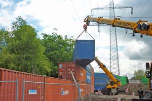 Wegen der nahen Hochspannungsleitung wurden die Container an der Emscher von zwei Kränen gestapelt
