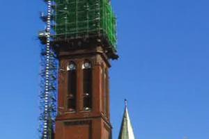 """<irspacing style=""""letter-spacing: -0.01em;"""">Kirchturm, 83 m Höhe, mit eingerüstetem Turmaufsatz und kombiniertem Material-und Personenaufzug. Das Gerüst ruht auf einem im obersten Turmgeschoss eingezogenen Trägerrost. Die Mitwirkung eines Hochbaustatikers und des Statikers einer Gerüstbaufirma sowie die Konsultation mit dem beauftragten Dachklempnermeister führten zum angestrebten Ergebnis</irspacing><span class=""""bildnachweis"""">Fotos: Ekkehart Hähnel</span>"""