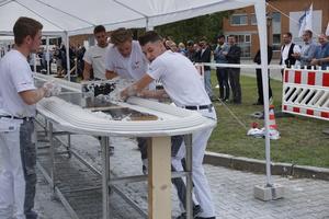 Teamwork: Ralph Lanz und Tobias Schmider ziehen die Schablone, während Julian Pinkau Material in den Händen bereithält, um Fehlstellen auszugleichen