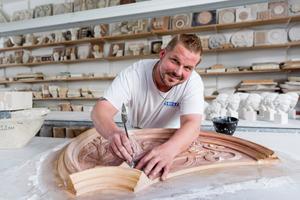 Miarbeiter Stefan Nötzold bei der Restaurierung einer Stuckrosette