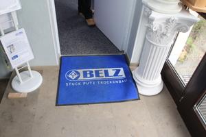 Die Mitarbeiter von Stuck-Belz bringen zum Kunden eigene Fußmatten mit