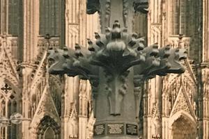 """Mit dem Modell der Kreuzblume vor dem Dom, eines der meistfotografierten Objekte Kölns, hat sich """"Stuck-Belz"""" ein Denkmal geschaffen. Auf dem Foto sieht man links das Ehepaar Kristen, das den Bau des Modells zu einem Großteil finanziert hat sowie den ehemaligen Werkstattleiter Hermann Klein und den aktuellen Werkstattleiter Hans Voosen"""