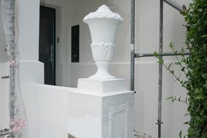 Den Hauseingang markiert eine Vase als Zierelement
