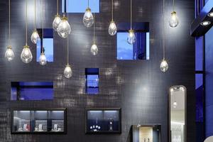 """Das zweigeschossige Atrium bildet das Zentrum des Juweliergeschäftes. Hier hängen große """"Tropfen"""" aus mundgeblasenem Glas unter einem vergoldeten Beleuchtungskörper<br />"""