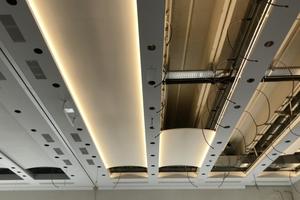 Detail der konkav geformten Metall-V-Akustikdeckensegel mit dahinter installiertem Kühl- und Heizsystem
