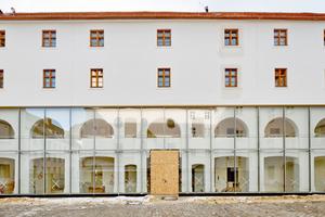 In der Glasfassade des Eingangsbereiches spiegelt sich das Sgraffito-Muster der Hofkirche