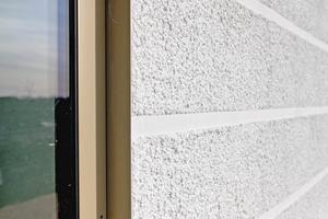Etwa 2,5 cm breite Strukturlinien im Putz geben der Fassade des Westflügels eine Gliederung