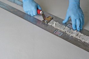 Auf den noch feuchten, glatten Putz wird die breitenverstellbare Listelschiene als Schablone gelegt. Mit einem Listelwerkzeug lassen sich Bossen schneiden