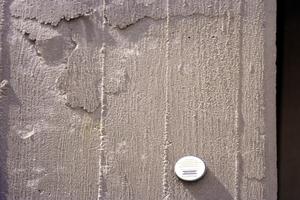 Stahlbetonstütze mit Aufwölbungen infolge Rostdruck der Bewehrung. Haftmagnet lässt Betondeckung ≤ 8 mm erkennen