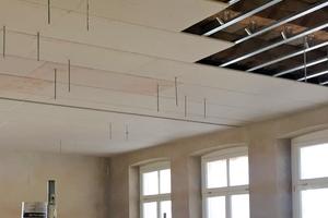 Durch die mit Gipskartonplatten beplankte Abhangdecke stoßen Stahlrundstäbe, an denen später Akustiksegel befestigt wurden