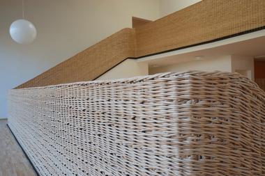 Für das Treppengeländer der zweigeschossigen Halle entschied sich Architekt Anton Mang für ein Geflecht aus heller geschälter Weide