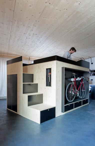 """Für die oberbayerische Wohnungswirtschafts-Gesellschaft B&O Gruppe entwarf der Designer Nils Holger Moormann eine modular aufgebaute Box als Raum im Raum, über deren """"Schubladentreppe"""" man zum Schlafplatz in 2 m Höhe gelangt"""