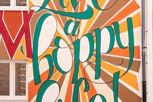 """""""Carpe diem & live a hoppy life!"""" lautet der Appell, der sich an alle Betrachter richtet. Dass an der Fassade """"hoppy"""" mit """"o"""" statt mit a geschrieben steht, ist eine Anspielung auf den Hopfen, der zum Bierbrauen verwendet wird"""