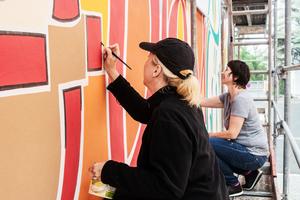 Kalligraphin Andrea Wunderlich (links) wurde bei der Ausführung von Malermeisterin Beate Ripka vom Caparol FarbDesignStudio unterstützt