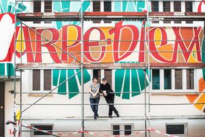 Etwa 15 x 9 m misst die Fassadenfläche, die von Andrea Wunderlich (rechts) nach ihrem eigenen künstlerischen Entwurf kalligrafisch gestaltet wurde. Links: Malermeisterin Beate Ripka vom Caparol FarbDesignStudio