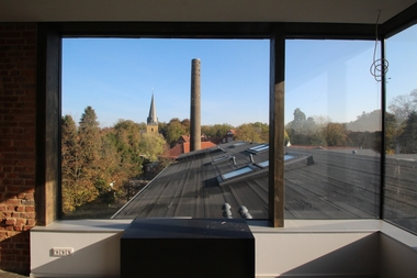 Durch die großen Fenster der Eventküche geht der Blick über die wieder hergestellten, mit Dachpappe gedeckten Dachflächen