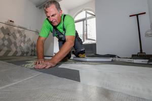 """Auf dem grundierten Boden werden die strukturierten textilen Fliesen im Sechskant-Format mit dem Dispersionsklebstoff """"Uzin KE 2000 S"""" verlegt<br />"""