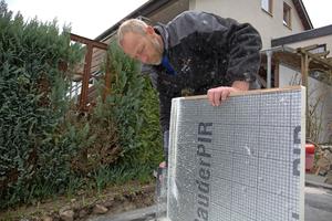 """Thomas Straub von der Dachdeckerfirma Karl Stahl Bedachungen aus Sigmaringen schrägt einen alukaschierten PIR-Dämmstoff im Freischnitt an <span class=""""bildnachweis""""></span>"""