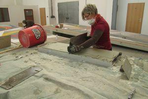 Auf die Rückseiten der Mosaikplatten trugen die Restauratoren den Versatzmörtel auf