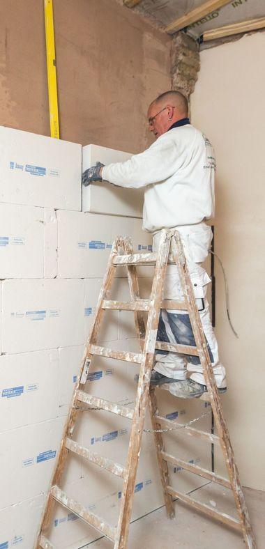 """Auf die egalisierte Wand klebten die Handwerker das Innendämmsystem """"Knauf Rotkalk in-Board"""" aus diffusionsoffenem Perlitgestein vollflächig auf<br />Fotos: Knauf / Stephan Klonk"""