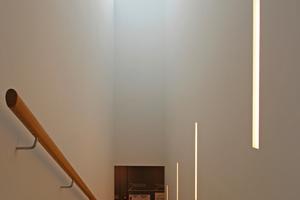 Der aus Stahl konstruierte Erschließungsturm der Treppe ist mit einer Glasplatte abgedeckt, so dass Tageslicht von oben durch den Erschließungsturm bis in das Erdgeschoss flutet