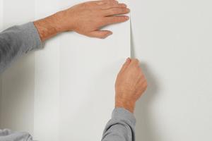 Kleber auf die Wand auftragen, Vliestapete auf Stoß ins nasse Kleberbett einlegen