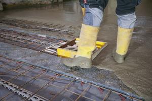 Der Beton wird eingepumpt und mit Schwabbelstangen grob und fein verdichtet und auf Sollhöhe verteilt. Flächen, in denen Leitungen oder Kanäle verlaufen, werden ausgespart