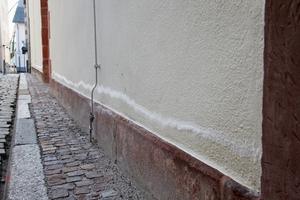 Die Außenwand des Karmeliterklosters in Frankfurt, das mit dem Feuchteregulierungsputzsystem Exzellent instandgesetzt worden ist, zeigt einen Salzschleier leicht oberhalb des SockelvorsprungsFotos: MC-Bauchemie