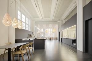 In der Kantine im vierten Obergeschoss verbinden sich die grauweiß eingefärbten Holzwolle-Akustikplatten mit dem weiß gestrichenen Bestand, dem dunklen Gussasphalt und den schwarzen Einbauten in Trockenbauweise<br />Fotos (2): Brigida González