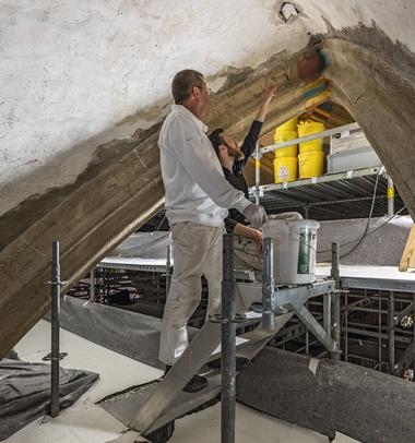 In 26 m Höhe wird die Gewölbedecke von Experten aufwändig in Handarbeit saniert