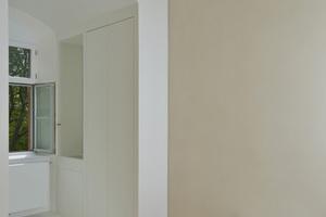 Die zusätzliche Wand bildet einen Zwischenraum. Der weiße schlichte Alkoven betont die reduzierte Raumgestaltung