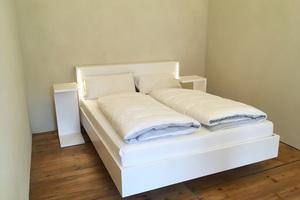 Das nahezu schwebende Bett betont die Leichtigkeit des Raumes