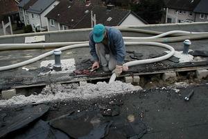 Verfüllen eines zweischaligen Flachdaches mit Dämmstoff