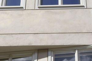 Die bündig in der Fassade liegenden, hellgraugrün lackierten Kastenfenster werden durch eine feine Putzlineatur umfasst