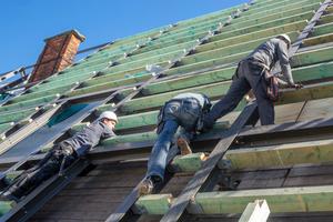 In das neue Dachtragwerk aus Stahl fügen die Handwerker außen Balken ein