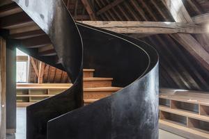 Auf die Galerieebene im Dachgeschoss führt unter anderem eine Spindeltreppe mit Wangen aus schwarzem Stahl