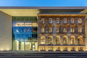 Die neoklassizistische Bestandsfassade wird vom Neubau mit seiner Glas- und Sandsteinfassade eingerahmt