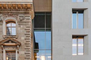 """Die Neubau- und Bestandsfassade werden gleichermaßen durch eine Glasfassade verbunden und getrennt<span class=""""bildnachweis"""">Foto: B+E Fotografie</span>"""